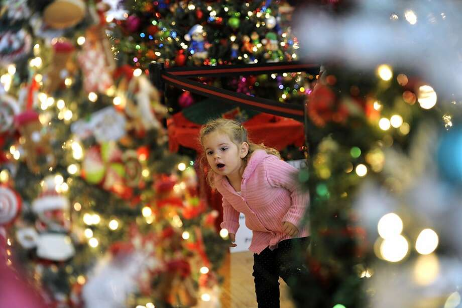 Three-year-old Carly Serepetti, of Allen Park, checks out the decorated Christmas trees on display at the the 28th annual Festival of Trees, at the Ford Community and Performing Arts Center in Dearborn, Mich., Sunday Nov. 25, 2012.  The festival is a benefit for the Children's Hospital of Michigan Foundation. (AP Photo/Detroit News, David Guralnick) Photo: David Guralnick, Associated Press