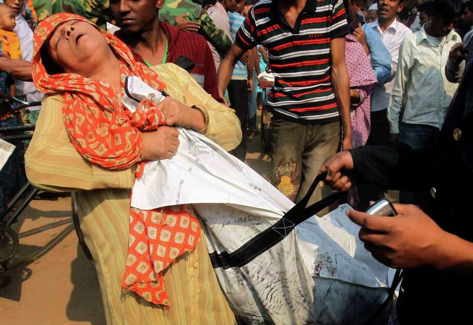 A Bangladeshi woman cries Sunday as she claims the body of her relative killed in a fire that raced through a garment factory outside Dhaka, killing 112 people. Photo: Jibon Amir, STR / AP