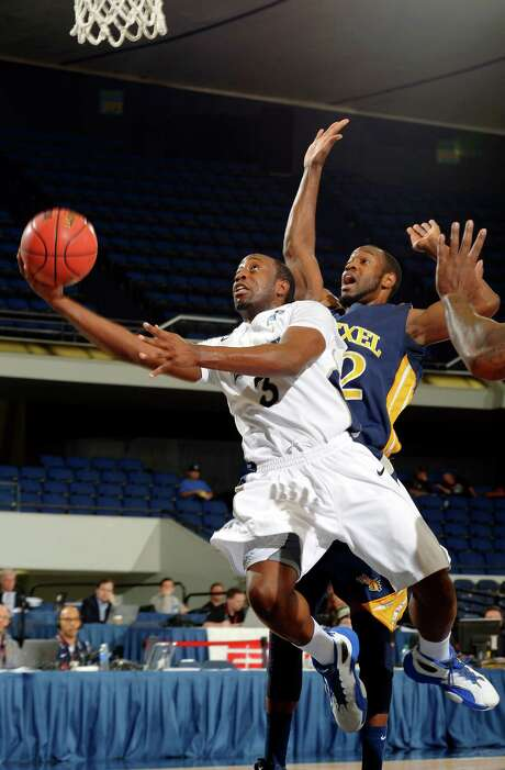 Tamir Jackson, driving past Drexel's Derrick Thomas, had 20 of Rice's 47 points Sunday. Photo: Mark J. Terrill, STF / AP