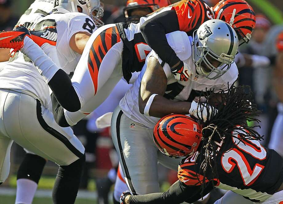 Oakland Raiders fullback Marcel Reese (45) is tackled by Cincinnati Bengals cornerback Terence Newman (23) and free safety Reggie Nelson (20) in the first half of an NFL football game, Sunday, Nov. 25, 2012, in Cincinnati. (AP Photo/Al Behrman) Photo: Al Behrman, Associated Press