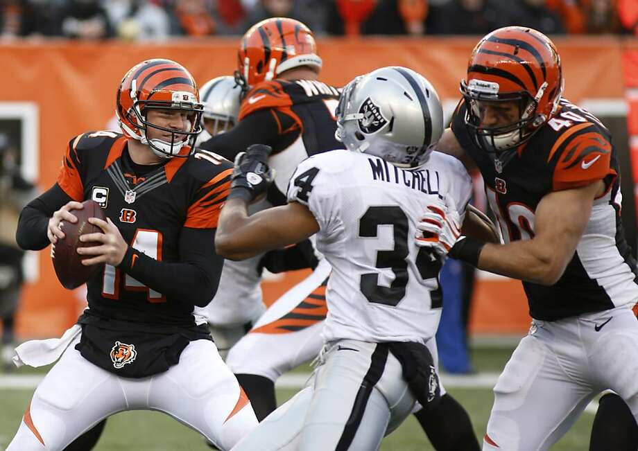 Cincinnati Bengals quarterback Andy Dalton (14) looks to pass against the Oakland Raiders in the second half of an NFL football game, Sunday, Nov. 25, 2012, in Cincinnati. Brian Leonard (40) blocks strong safety Mike Mitchell (34). Dalton threw three touchdown passes in the game won by Cincinnati 34-10. (AP Photo/David Kohl) Photo: David Kohl, Associated Press