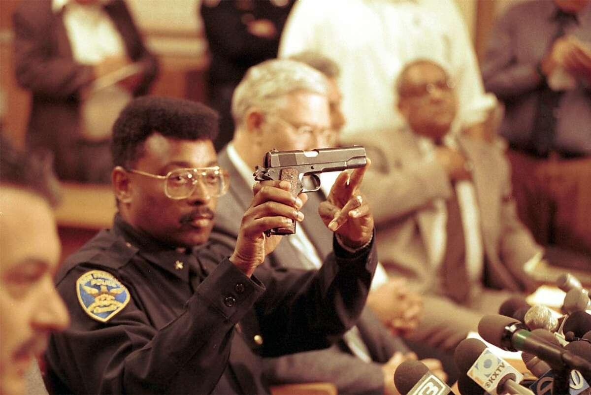 SFPD Cmdr. Richard Holder holds the gun that 101 California St. gunman, Gian Luigi Ferri, used to kill himself.