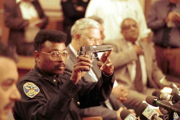 GUNMAN  Commander Richard Holder holds the gun that 101 California gunman, Gian Luigi Ferri, used to kill himself.   Photo by Vince Maggiora/The Chronicle 1993.