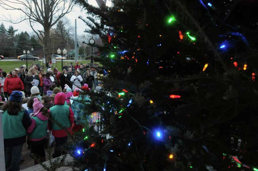 With the tree lights on, families sign Christmas songs during the annual tree lighting at Loudon Gre