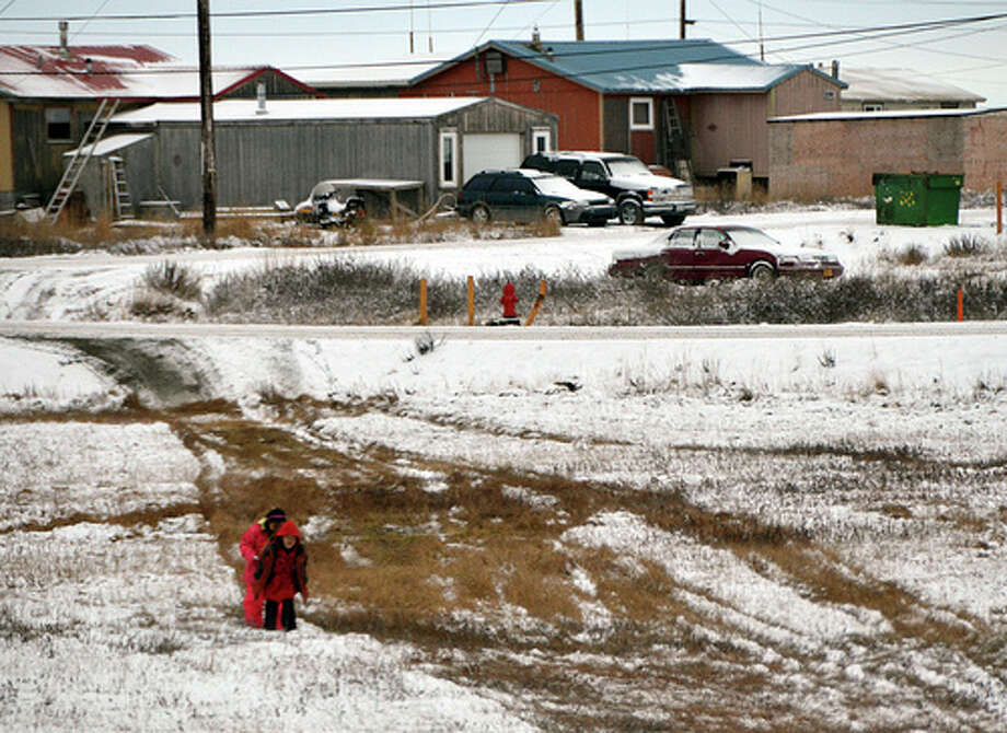 Two children walk home in Nuiqsut, Alaska. (Jennifer A. Dlouhy / The Houston Chronicle)