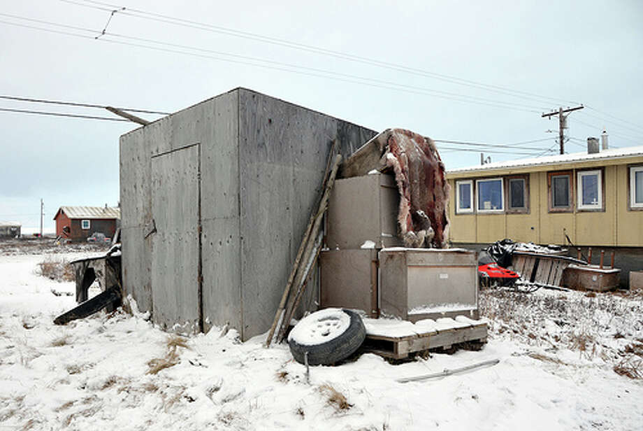 A wooden shack encloses the entrance to an underground ice cellar in Nuiqsut, Alaska.