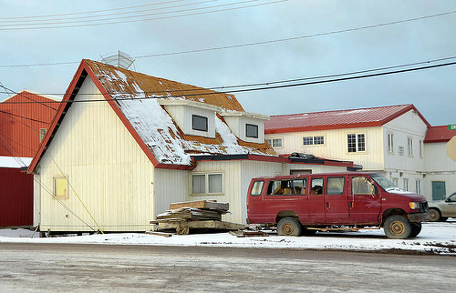 An old vehicle without glass in its windows is parked along buildings in Barrow, Alaska. Cars are expensive to transport to the North Slope. Once they are broken beyond repair, they tend to stay in the region, rusting in front yards and along the road. (Jennifer A. Dlouhy / The Houston Chronicle)