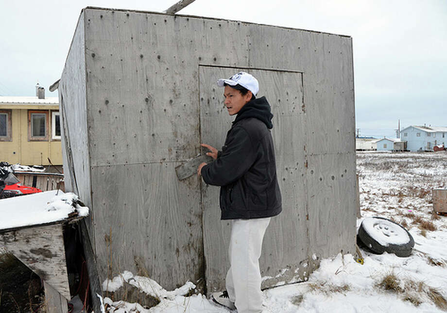 Thomas Napageak Jr. opens the door to the shack that protects his ice cellar. The cellar, tunneled into Alaska's tundra, is big enough to hold the meat from at least two whales, keeping it preserved for village-wide holiday feasts. (Jennifer A. Dlouhy / The Houston Chronicle)