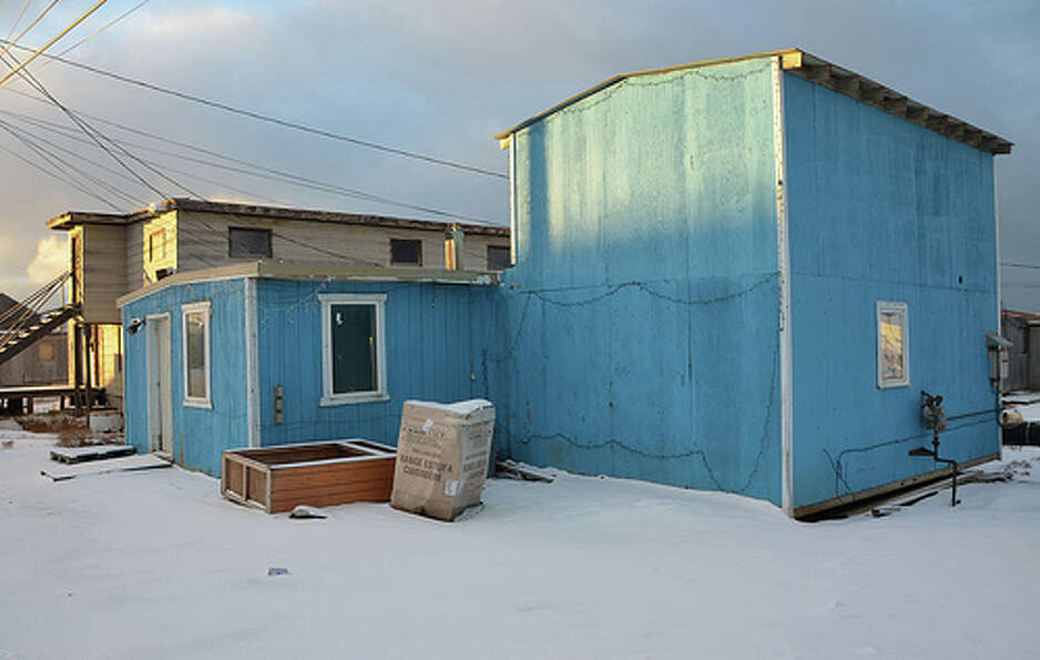 Many wooden houses in Barrow, Alaska are painted with bright colors, making them stand out against t