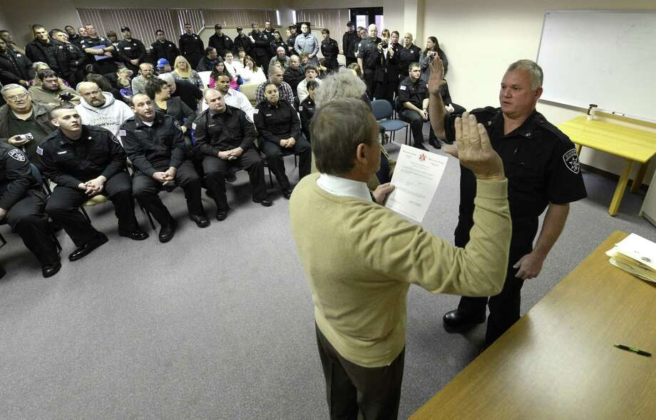 Rensselaer County Sheriff Jack Mahar swears in Scott Newell  the first of 10 new corrections officers in a ceremony at the Rensselaer County Jail in Troy, N.Y. Nov 26, 2012.   (Skip Dickstein/Times Union) Photo: SKIP DICKSTEIN / 00020243A