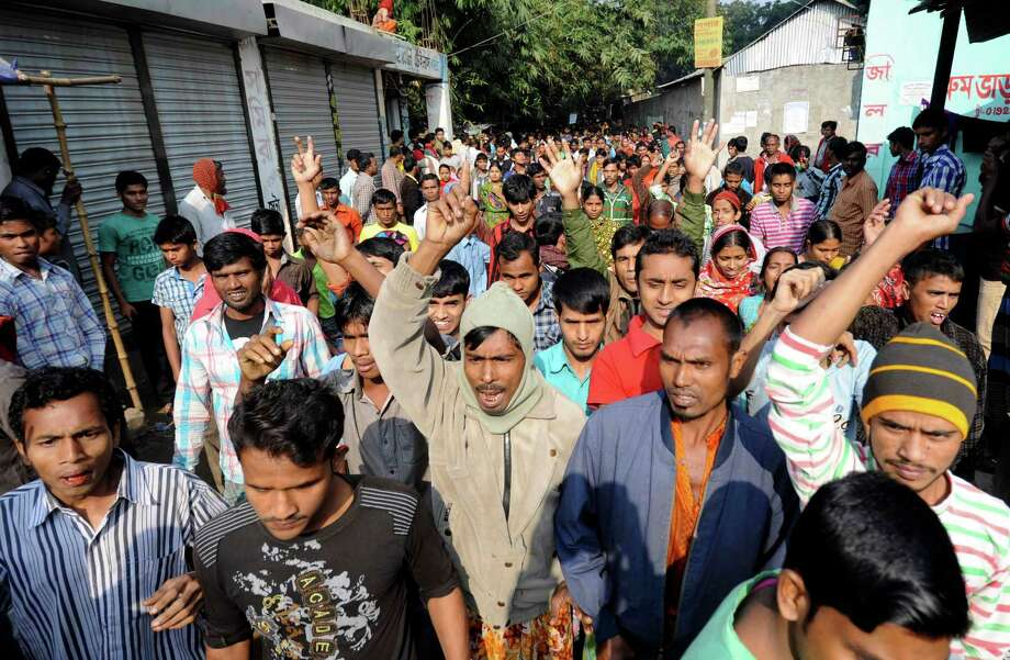 Bangladeshis take to a protest through the streets Monday, Nov. 26, 2012 after a garment factory fire killed more than 110 people Saturday on the outskirts of Dhaka, Bangladesh. Bangladeshis Monday blocked the streets near Dhaka, throwing stones at factories and smashing vehicles, as they demanded justice for those killed in the fire. Saturday's blaze highlighted unsafe conditions in an industry producing for retailers around the world. Photo: AP / AP