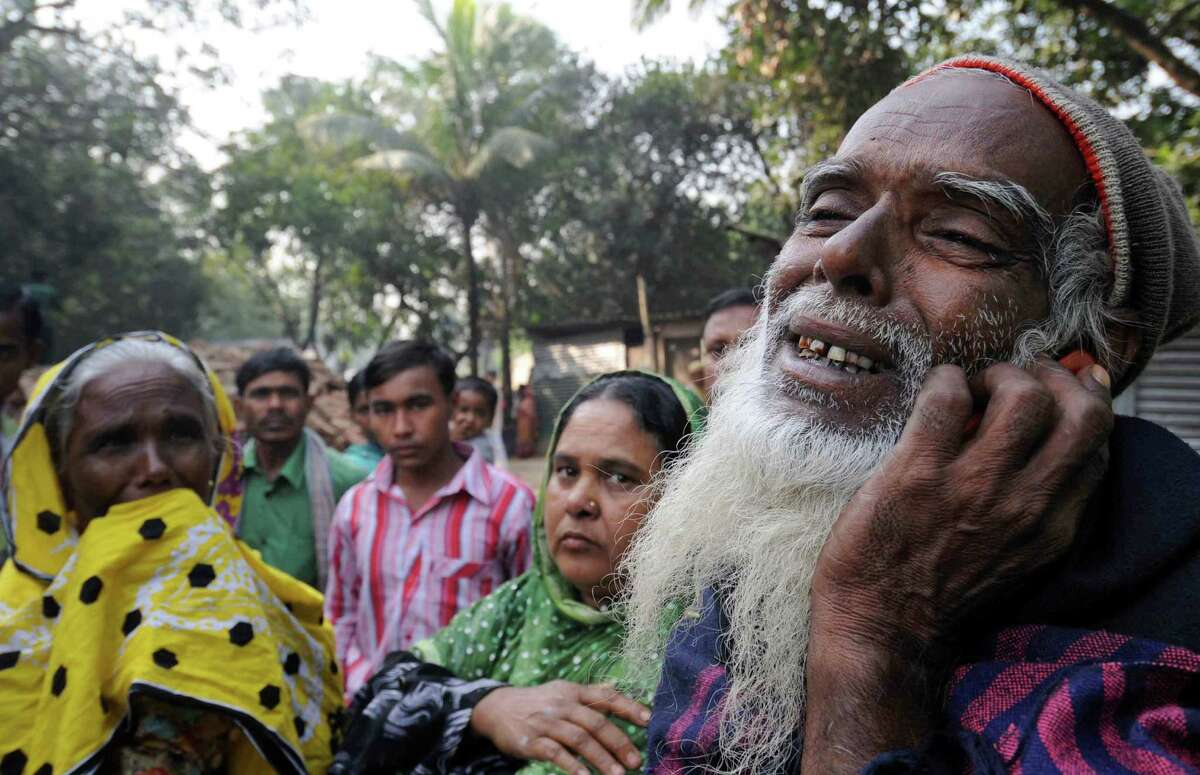 A Bangladeshi man, right, reacts as he looks for his son's body outside a garment factory where a fire killed more than 110 people Saturday on the outskirts of Dhaka, Bangladesh, Monday, Nov. 26, 2012. Bangladeshis Monday blocked the streets near Dhaka, throwing stones at factories and smashing vehicles, as they demanded justice for those killed in the fire. Saturday's blaze highlighted unsafe conditions in an industry producing for retailers around the world.