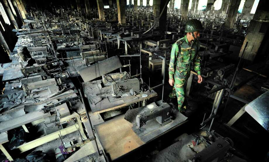 A Bangladeshi police officer walks between rows of burnt sewing machines in a garment factory outside Dhaka, Bangladesh, Sunday, Nov. 25, 2012. At least 112 people were killed in a late Saturday night fire that raced through the multi-story garment factory just outside of Bangladesh's capital, an official said Sunday. Photo: Khurshed Rinku, AP / AP