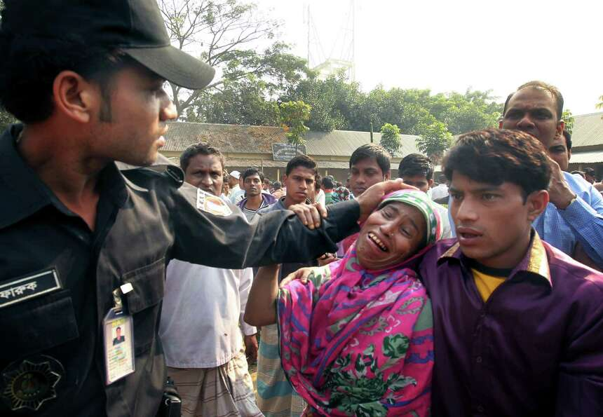 A Bangladeshi policeman consoles a woman whose relative was killed in a fire at a garment factory ou