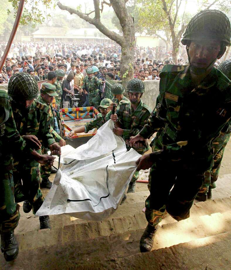 Bangladeshi army soldiers carry the bodies of workers killed in a fire at a garment factory outside Dhaka, Bangladesh, Sunday, Nov. 25, 2012. At least 112 people were killed in a late Saturday night fire that raced through the multi-story garment factory just outside of Bangladesh's capital, an official said Sunday. Photo: Jibon Amir, AP / AP