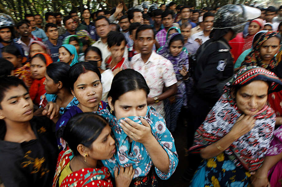 People look at a burnt garment factory outside Dhaka, Bangladesh, Sunday, Nov. 25, 2012. At least 112 people were killed late Saturday night in a fire that raced through the multi-story garment factory just outside of Bangladesh's capital, an official said Sunday. Photo: Hasan Raza, AP / AP