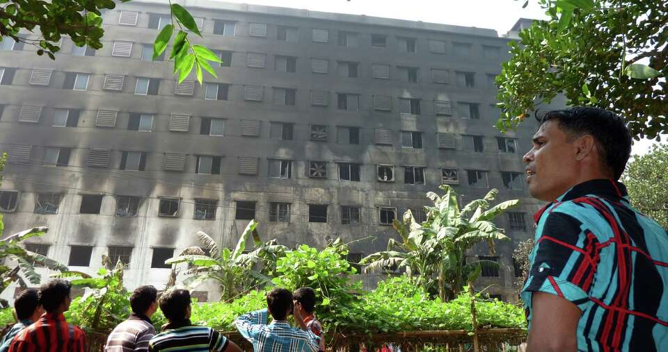Bangladeshi pedestrians look at the damaged nine-story Tazreen Fashion plant in Savar, about 30 kilo