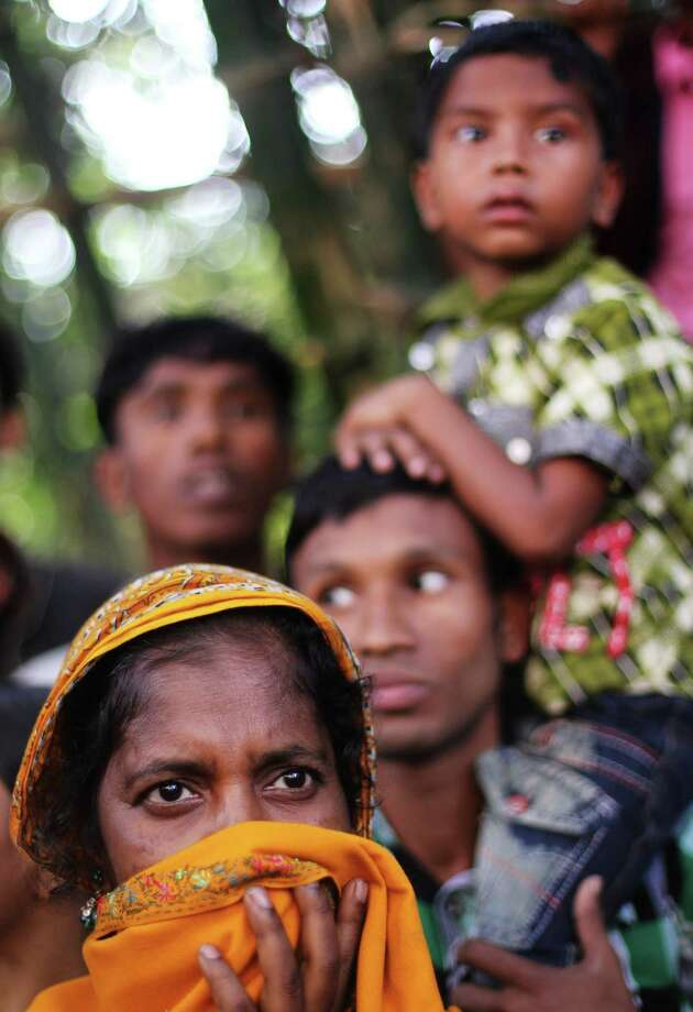 """Bangladeshi Zulekha Begum waits to talk to police to try and get information regarding her younger sister who was killed in a garment factory that was destroyed in a fire the day before in Savar, about 30 kilometres north of Dhaka on November 26, 2012. Garment workers staged mass protests to demand the end to """"deathtrap"""" labour conditions after Bangladesh's worst-ever textile factory fire, as a new blaze sparked fresh panic and terror. Ahead of the first of a series of mass funerals for the 110 victims, survivors of Saturday night's blaze joined several thousand colleagues to block a highway and march in the manufacturing hub of Ashulia.  AFP PHOTO/ STRSTR/AFP/Getty Images Photo: STR, AFP/Getty Images / AFP"""