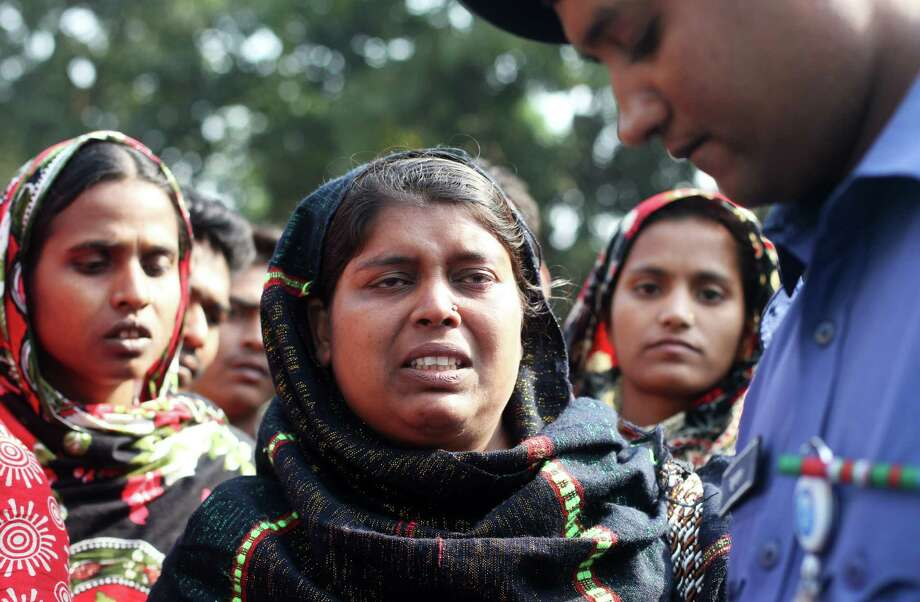 "Bangladeshi Sabiha Khatun (C) speaks to police about her missing younger sister who was a worker in a garment factory that burned the day before in Savar, about 30 kilometres north of Dhaka on November 26, 2012. Garment workers staged mass protests to demand the end to ""deathtrap"" labour conditions after Bangladesh's worst-ever textile factory fire, as a new blaze sparked fresh panic and terror. Ahead of the first of a series of mass funerals for the 110 victims, survivors of Saturday night's blaze joined several thousand colleagues to block a highway and march in the manufacturing hub of Ashulia.  AFP PHOTO/ STRSTR/AFP/Getty Images Photo: STR, AFP/Getty Images / AFP"