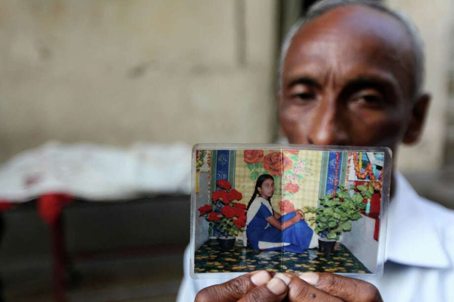 "Bangladeshi Mohammad Ali holds up a photograph of his missing daughter who worked at a garment factory that burned down the day before, at the Dhaka Medical College Hospital, in Dhaka on November 26, 2012. Garment workers staged mass protests to demand the end to ""deathtrap"" labour conditions after Bangladesh's worst-ever textile factory fire, as a new blaze sparked fresh panic and terror. Ahead of the first of a series of mass funerals for the 110 victims, survivors of Saturday night's blaze joined several thousand colleagues to block a highway and march in the manufacturing hub of Ashulia.  AFP PHOTO/ STRSTR/AFP/Getty Images Photo: STR, AFP/Getty Images / AFP"
