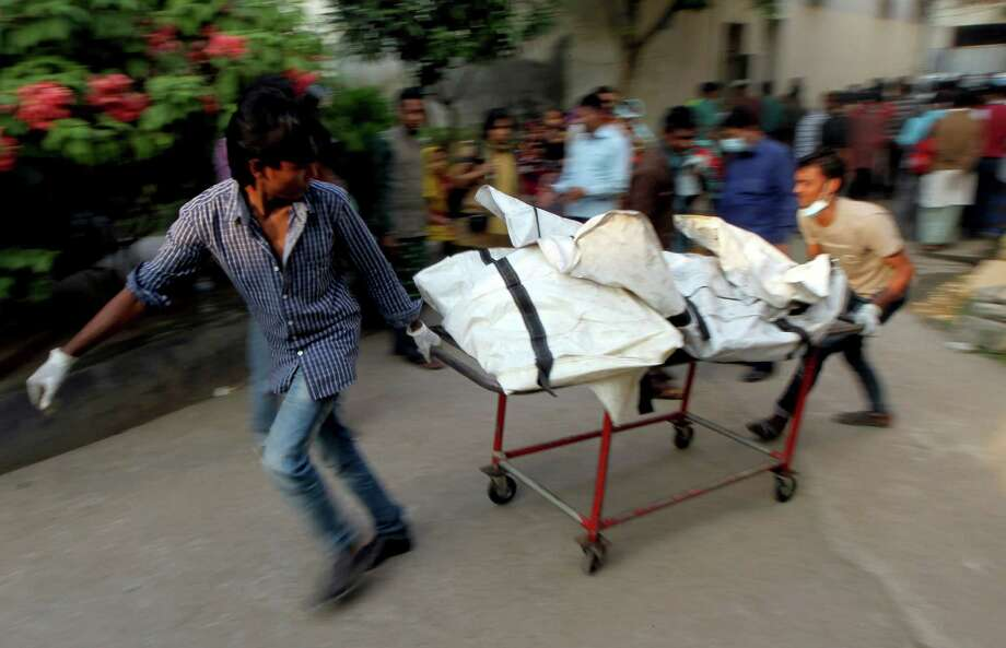 "Bangladeshi health workers carry the remains of victims, from a garment factory that burned down, to a lab for forensic testing at the Dhaka Medical College Hospital in Dhaka on November 26, 2012. Garment workers staged mass protests to demand the end to ""deathtrap"" labour conditions after Bangladesh's worst-ever textile factory fire, as a new blaze sparked fresh panic and terror. Ahead of the first of a series of mass funerals for the 110 victims, survivors of Saturday night's blaze joined several thousand colleagues to block a highway and march in the manufacturing hub of Ashulia.  AFP PHOTO/ STRSTR/AFP/Getty Images Photo: STR, AFP/Getty Images / AFP"