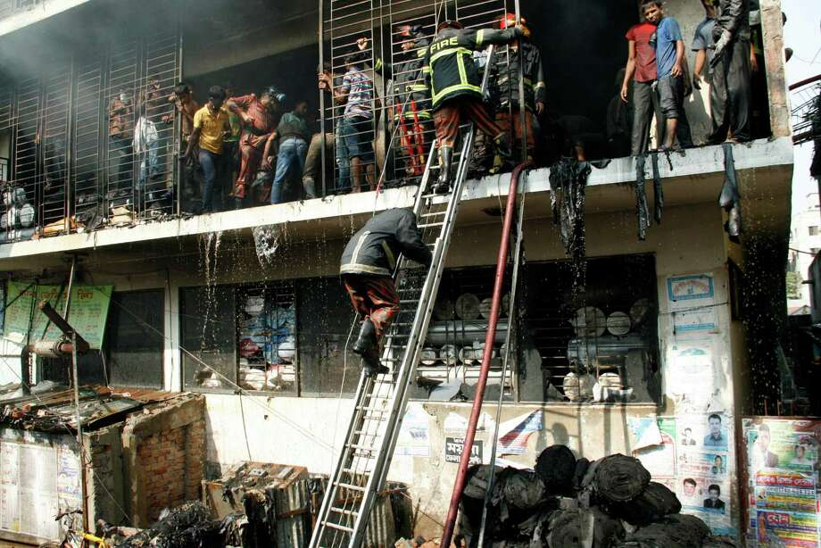 Bangladeshi firefighters and workers try to douse the fire at a garment-factory in Dhaka, Bangladesh, Monday, Nov. 26, 2012  two days after a similar incident killed more than 110 people on the outskirts. No casualty was reported in Monday's fire.   Bangladeshis were Monday blocking the streets near Dhaka, throwing stones at factories and smashing vehicles, as they demanded justice for those killed in Saturday's  fire. Photo: AP / AP