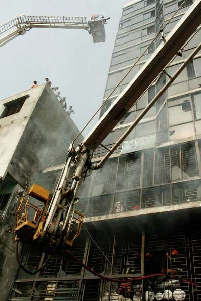 Bangladeshi firefighters try to douse the fire at a garment-factory in Dhaka, Bangladesh, Monday, No