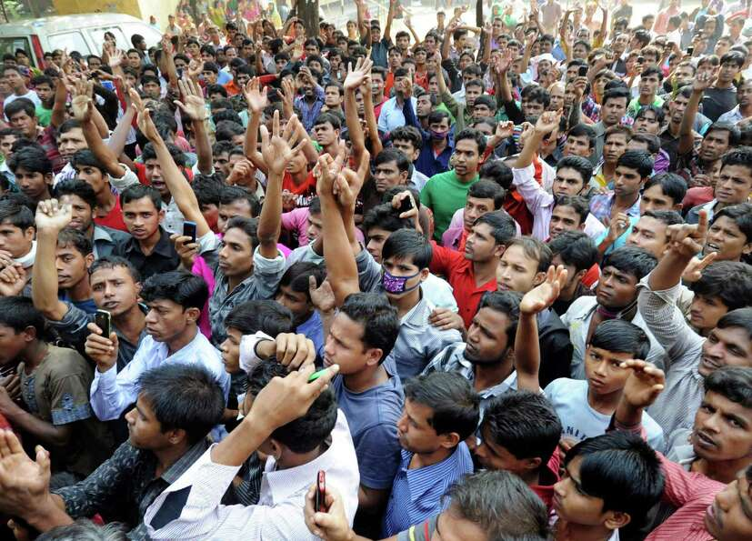 Bangladeshis protest outside a garment-factory where a fire killed more than 110 people Saturday on