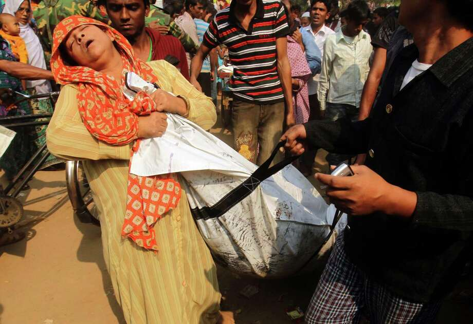 A Bangladeshi woman mourns as she holds the body of a relative who died in a fire in the nine-storey Tazreen Fashion plant in Savar, about 30 kilometres north of Dhaka on November 25, 2012.  Rescue workers in Bangladesh recovered 109 bodies on Sunday after a fire tore through a garment factory, forcing many workers to jump from high windows to escape the smoke and flames.  AFP PHOTOSTRINGER/AFP/Getty Images Photo: STRINGER, AFP/Getty Images / AFP