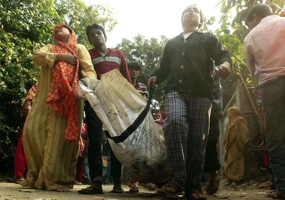 A Bangladeshi family carries the body of their relative died in a fire at a garment factory in the Savar neighborhood in Dhaka, Bangladesh, Sunday Nov. 25, 2012. At least 112 people were killed in a late Saturday night fire that raced through the multi-story garment factory just outside of Bangladesh's capital, an official said Sunday. Photo: Jibon Amir, AP / AP