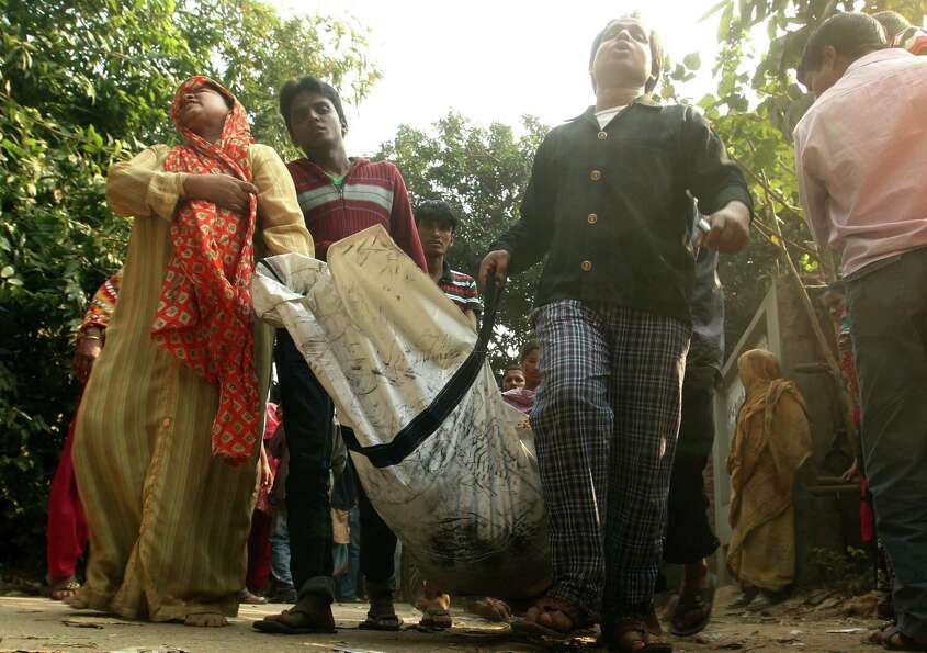 A Bangladeshi family carries the body of their relative died in a fire at a garment factory in the S