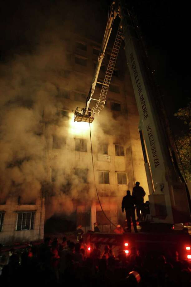 This picture taken on 24 November, 2012 shows Bangladeshi firefighters trying to extinguish a fire at the nine-storey Tazreen Fashion plant in Savar, about 30 kilometres north of Dhaka on November 25, 2012.  Rescue workers in Bangladesh recovered 109 bodies on Sunday after a fire tore through a garment factory, forcing many workers to jump from high windows to escape the smoke and flames.  AFP PHOTOSTRINGER/AFP/Getty Images Photo: STRINGER, AFP/Getty Images / HasanRaza