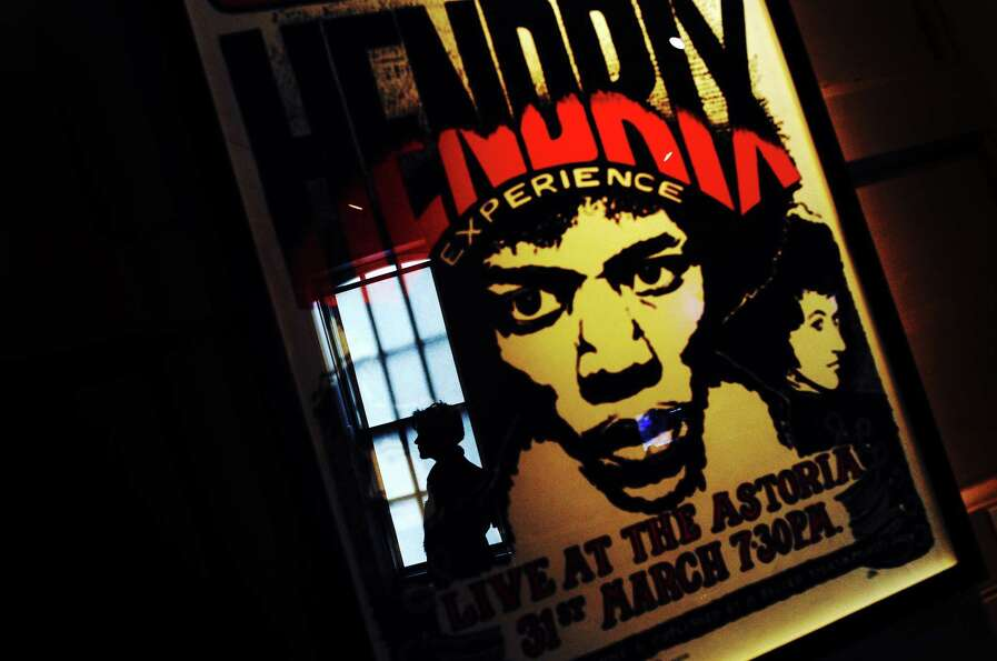 A person reflected in the glass of a framed poster advertising a Jimi Hendrix concert, at an exhibit