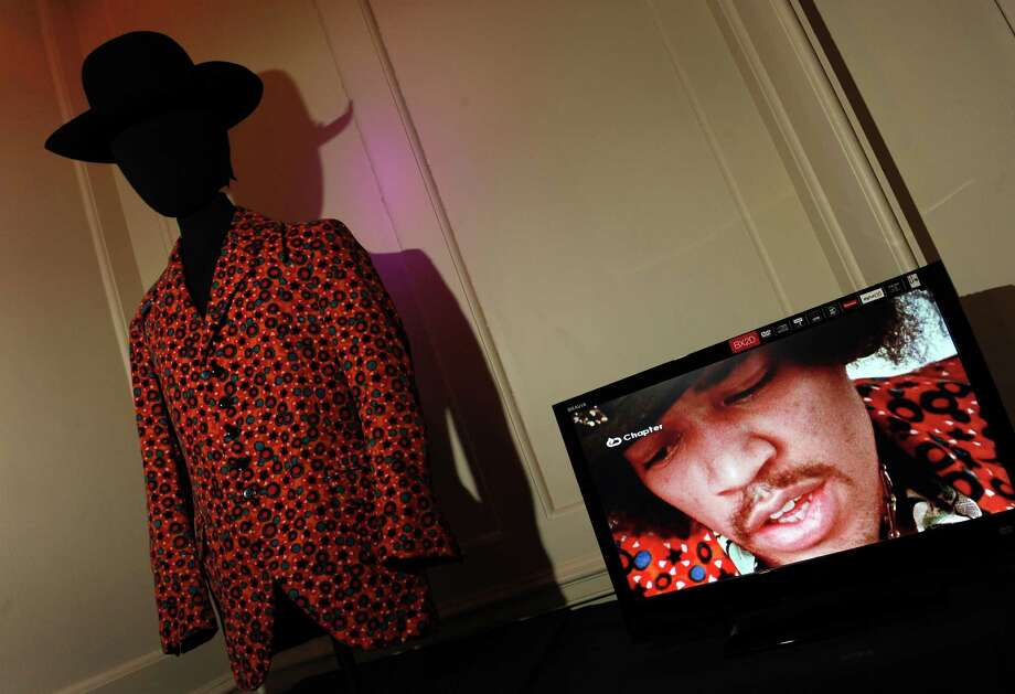 A monitor shows a video of  Jimi Hendrix beside a distinctive orange velvet jacket and Westerner hat worn by him, at The Handel House Museum in London on Aug. 24, 2010.        AFP PHOTO/ADRIAN DENNIS Photo: ADRIAN DENNIS, Getty / 2010 AFP