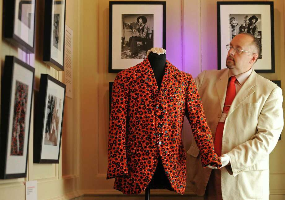 An employee poses for photographers with an orange velvet jacket once worn by  Jimi Hendrix, during a preview of the 'Hendrix in Britain' exhibition, at the Handel House Museum, in London on Aug. 16, 2010. .      AFP PHOTO/BEN STANSALL Photo: BEN STANSALL, Getty / 2010 AFP
