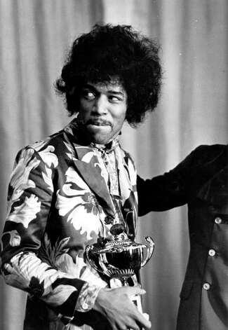 Jimi Hendrix holds an award which he has just received from Radio One DJ Jimmy Savile in England in 1967. Photo: Express, Getty / Hulton Archive