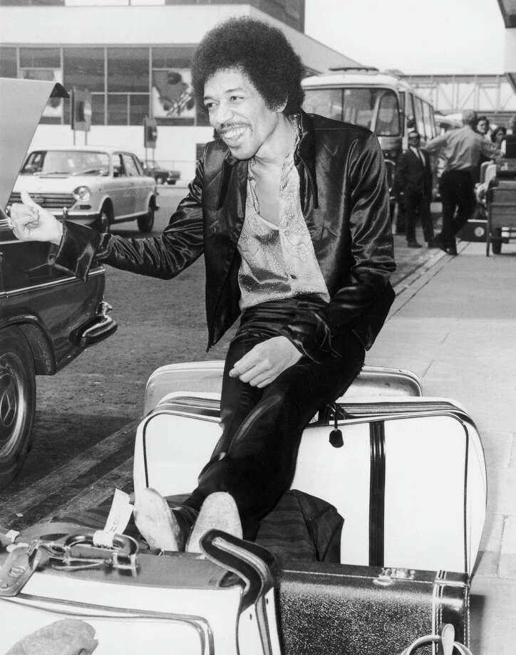 Jimi Hendrix jokingly thumbs for a lift while waiting with his baggage at Heathrow Airport, London, in 1968. Photo: Central Press, Getty / Hulton Archive