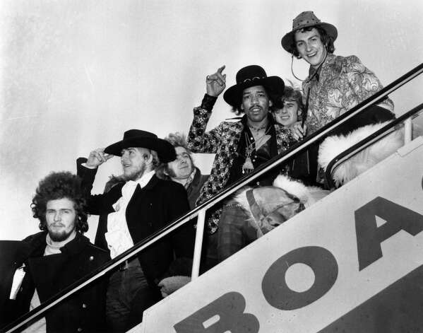 Jimi Hendrix and Mitch Mitchell of The Jimi Hendrix Experience wave goodbye as they board a plane in London, with assorted members of the Byrds, the Soft Machine and the Alan Price Set, in 1968. Photo: J. Wilds, Getty / Hulton Archive