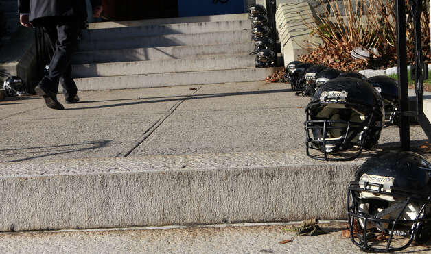 Football helmets line the stairs of Assumption Church during a funeral for former Ansonia High School football coach Jack Hunt in Ansonia, Conn. on Monday, November 26, 2012. Photo: BK Angeletti, B.K. Angeletti / Connecticut Post freelance B.K. Angeletti