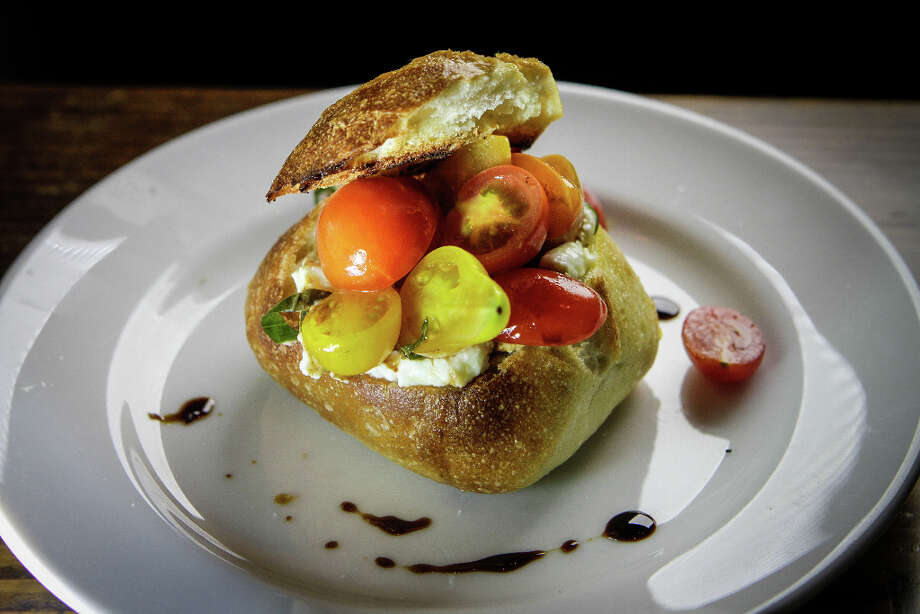 """.... and a burrata bowl ($9), a partly hollowed-out roll filled with the silken cheese, topped with cherry tomato halves and drizzled with balsamic. It was a good match for many wines on the list and would have been even better with a more restrained hand with the vinegar."" Photo: John Storey, Special To The Chronicle / John Storey"