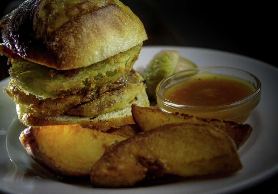 """To quash a hamburger craving, Simmons offers sliders (two for $8), a thick well-charred patty served with aged cheddar cheese, house-cured cucumbers and fried potato wedges."" Pictured here: The Fried Tomato Slider with Bacon. Photo: John Storey, Special To The Chronicle / John Storey"