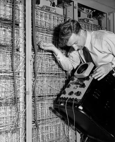 "A man checks the installation of the Elliott 402 'Electric Brain' at the British Instrument Industries Exhibition on June 27, 1955 at Earl's Court, London. The original caption for this photo boasted: ""This electronic computer can solve complicated mathematical problems in one hour."" Photo: Derek Berwin, Getty Images / Hulton Archive"