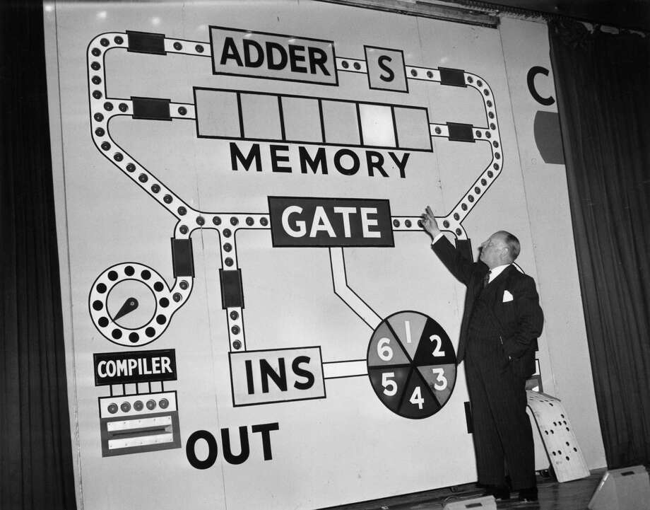 H A Thomas, manager of the Instrumentation and Control section of Unilever's engineering department, gives the Faraday lecture on January 26, 1959  at London's Festival Hall. His subject is 'Automation' and here he demonstrates the workings of an electronic calculator or computer. Photo: Jimmy Sime, Getty Images / Hulton Archive