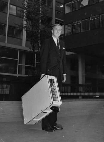 A man demonstrates a suitcase-sized computer from the Elliot Automation Group, in Britain, on January 1, 1966. Photo: Evening Standard, Getty Images / Hulton Archive