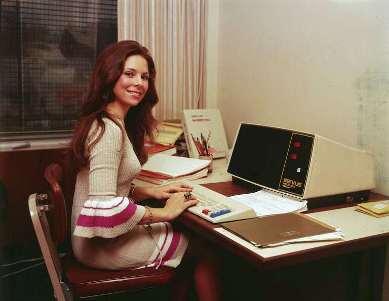 A woman works at an early model Servus desktop computer in the 1970s.