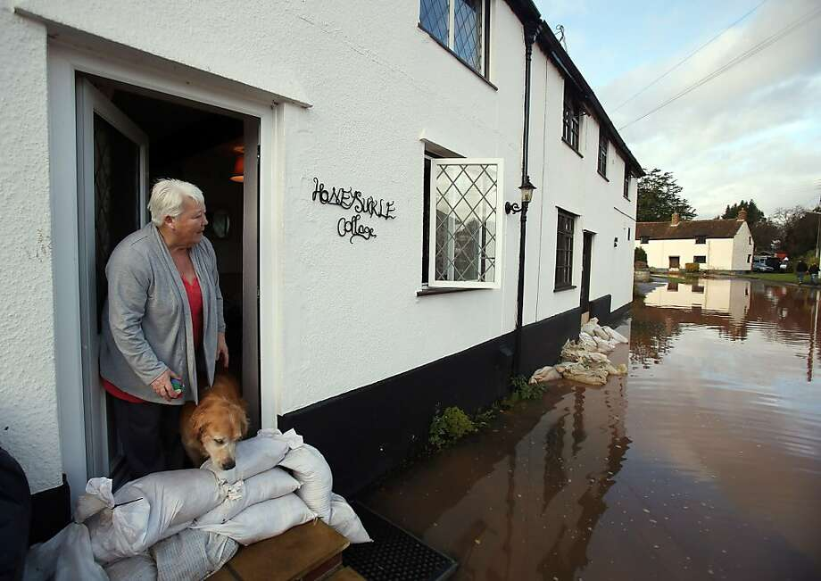 So much for my walk: Anne Bartlett and Henry the dog look out from their doorstep in the flooded  village of Ruishton in Somerset, England. Heavy rain caused flooding in many parts of the country, particularly the southwest. Photo: Matt Cardy, Getty Images