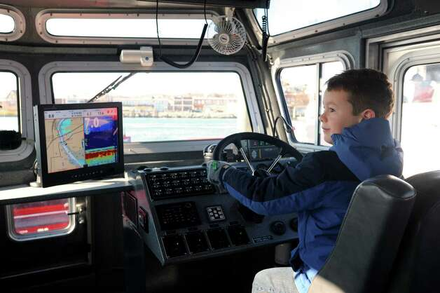 Norwalk Fire Department held a ceremony commissioning their new Fire Boat Marine Unit 238, the Robert Bedell, in honor of firefighter Bedell who served the Department with distinction from 1975 until his untimely death in 2004. Bedell's grandson, Robert Bedell takes a turn at the wheel of the vessell after the cermony at Veterans Memorial Park on Monday, Nov. 26, 2012 in Norwalk, Conn. Photo: Cathy Zuraw / Connecticut Post