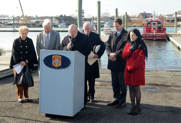 Monsignor William Scheyd, the Norwalk Fire Department Chaplain delivers the invocation at the ceremony commissioning Norwalk's new Fire Boat Marine Unit 238 at Veterans Memorial Park on Monday, Nov. 26, 2012 in Norwalk, Conn. Also taking part, left to right, Chairwoman of the Fire Commission Carol Andreoli, Mayor Richard Moccia, Fire Chief Denis McCarthy, Congressman Jim Himes and State Representative Gail Lavielle. The vessel was named the Robert Bedell in honor of firefighter Bedell who served the Department with distinction from 1975 until his untimely death in 2004. Photo: Cathy Zuraw / Connecticut Post