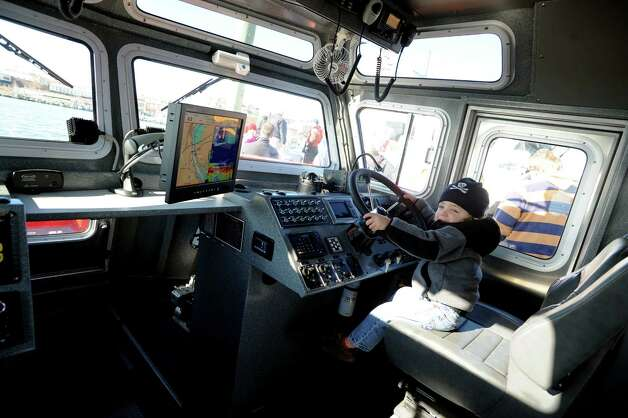 Reid Maggio sits at the wheel of the newly commissioned Fire Boat Marine Unit 238, the Robert Bedell. The ceremony at Veterans Memorial Park on Monday, Nov. 26, 2012 in Norwalk, Conn. named the vessel in honor of firefighter Bedell who served the Department with distinction from 1975 until his untimely death in 2004. Photo: Cathy Zuraw / Connecticut Post