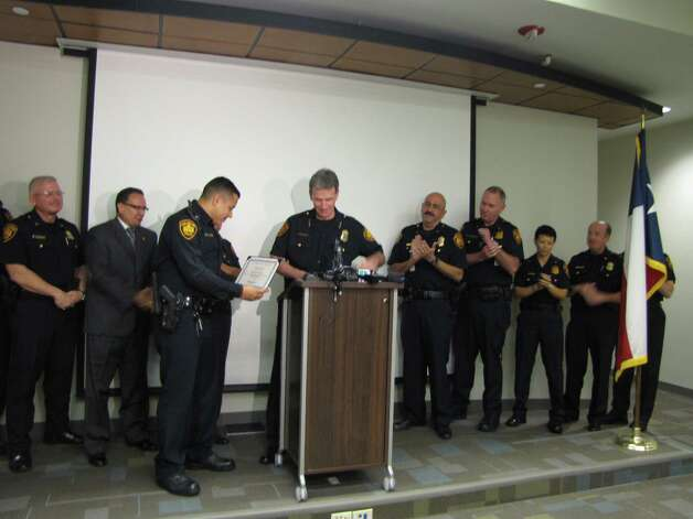 San Antonio Police Chief William McManus awards Officer German Huerta on Monday, Nov. 26, 2012, with a certificate of merit after he reportedly rescued an 18-year-old girl from a burning vehicle on Saturday. Photo: Ana Ley